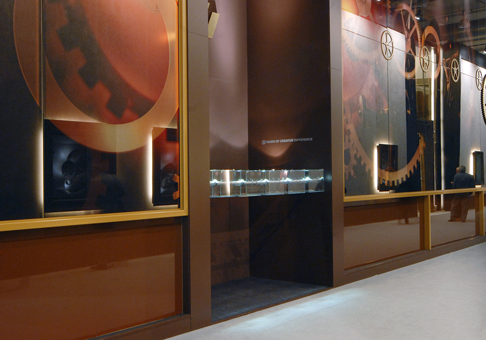 Baselworld booth with tower display cases on steel structure with exclusive soft dark-hued rust finish and suspended showcases.